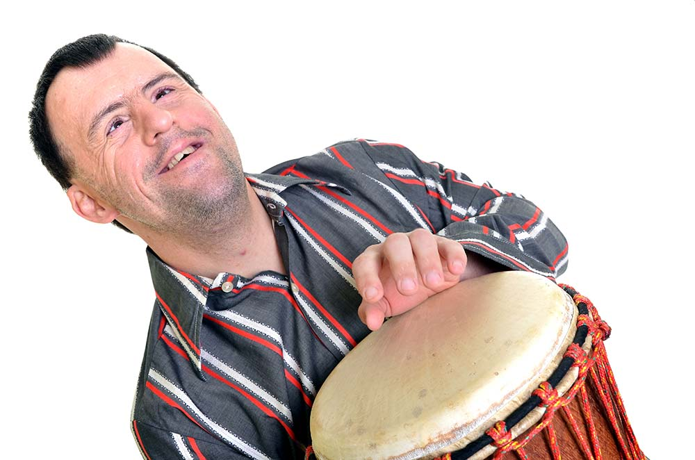 man with Down's syndrome playing with African percussion
