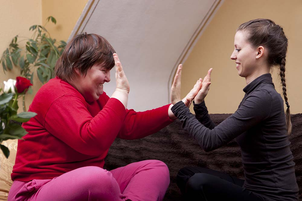 Two women, one of them disabled, are doing rhythm exercises